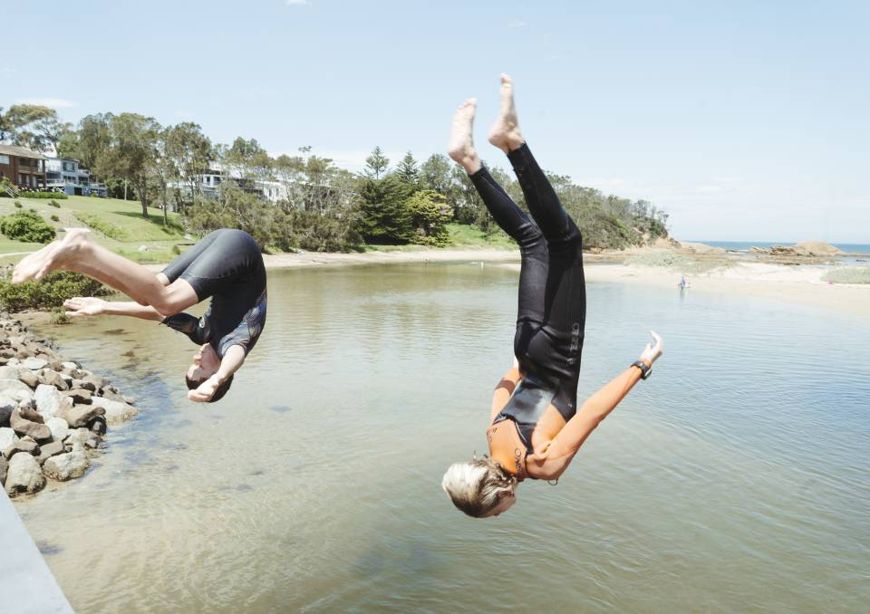 Children holidaying at Broulee last week perfect their jumps off the bridge over Candlagan Creek. But the Sydney COVID-19 outbreak has caused uncertainty for summer plans as south coast businesses record numerous cancellations. Picture: Dion Georgopoulos