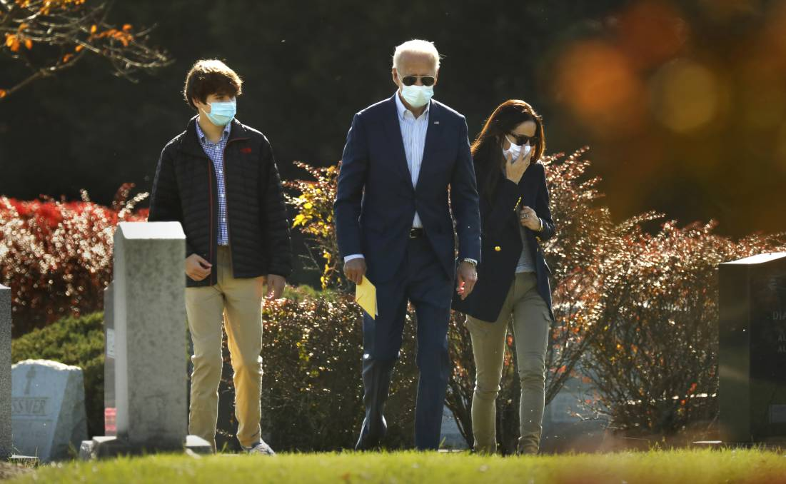 President-elect Joe Biden visits the grave of his son Beau Biden in Wilmington, Delaware, yesterday, along with his grandson Hunter Biden, left, son of Beau Biden, and his daughter-in-law Hallie Biden, right (wife of Beau Biden). Picture: Getty Images