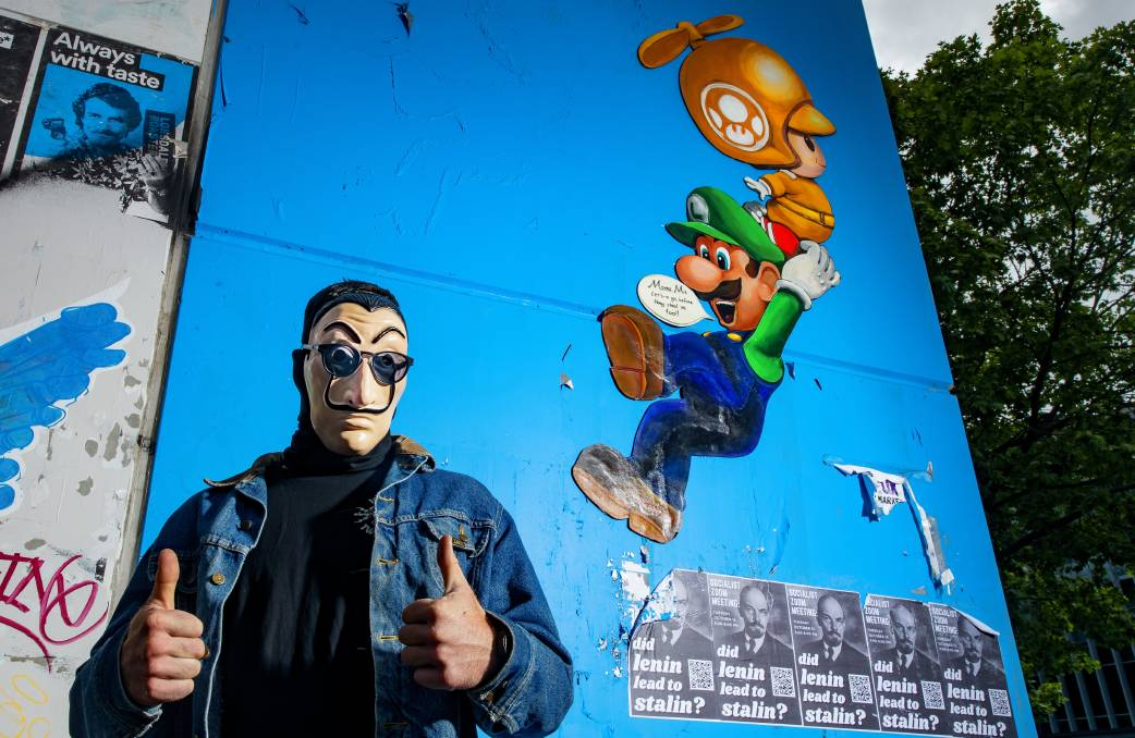 Street artist 'Johnny Sayless' is pictured with his Mario Kart work in Braddon. Picture: Sitthixay Ditthavong