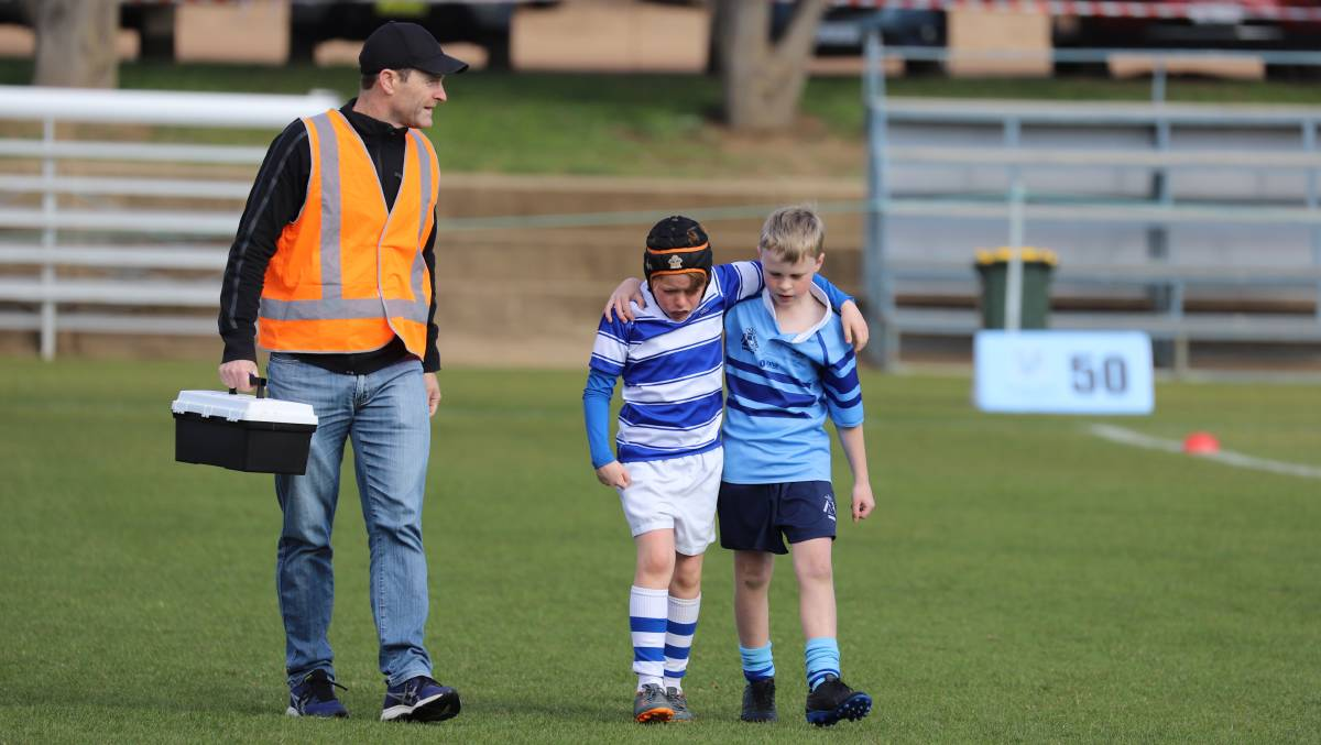 St Eddie's player Brody Grainger, 9, comforted by Marist opponent Theo Campton, 10, with Dr Michael Koppman. Picture: Kelly Grainger