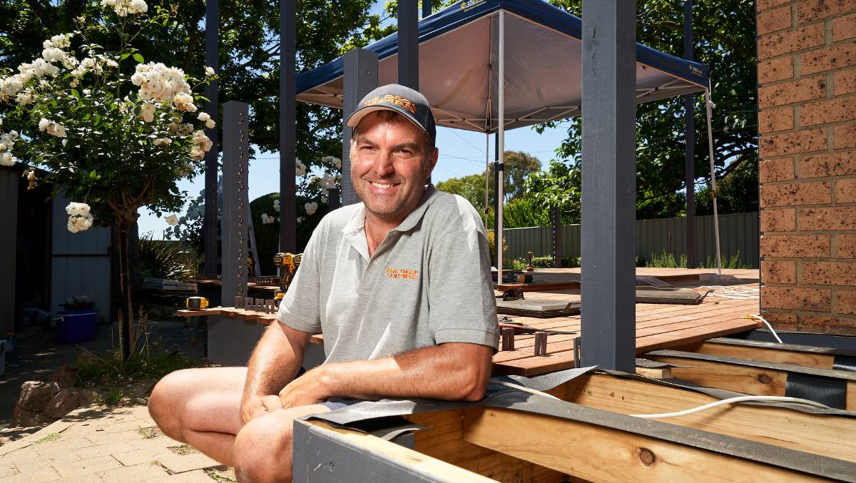 Richard Kent, working on a deck in Florey, says demand for decks and pergolas has customers waiting until April for new work. Picture: Matt Loxton