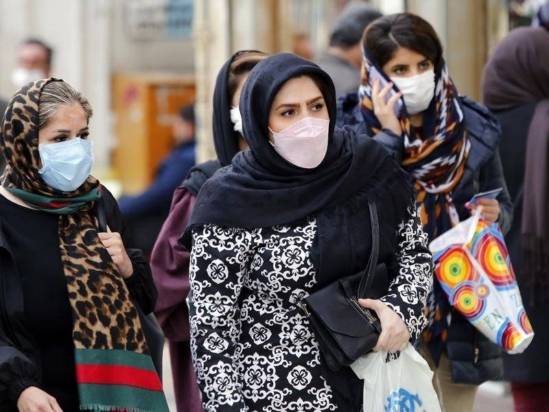 Iranians wearing face masks in Tehran as the country grapples with a growing COVID-19 death toll.