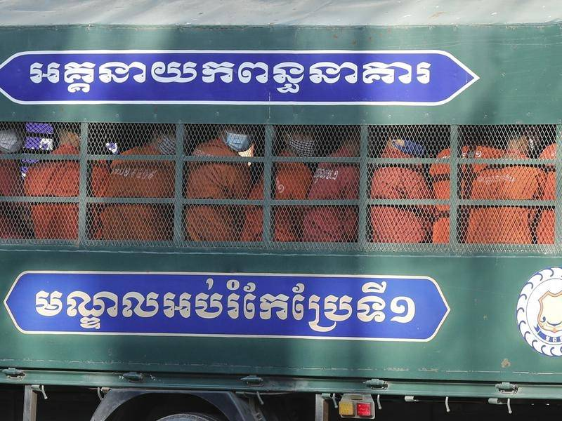 Former activists of the Cambodia National Rescue Party are taken to court in a police truck.
