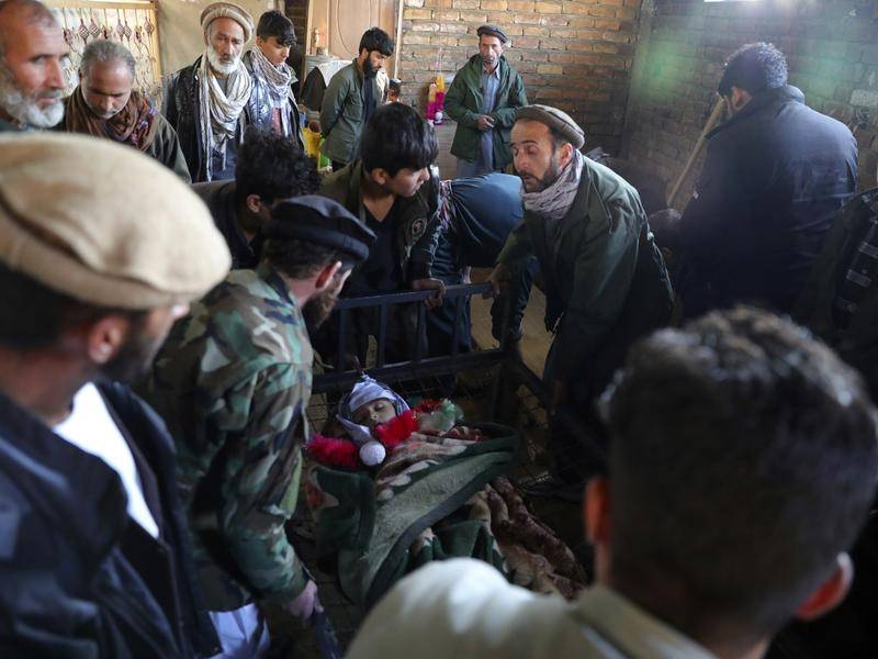Relatives stand around the dead body of a boy killed by the mortar shell attack in Kabul.