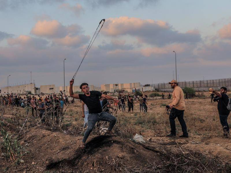 A Palestinian slings a stone at Israeli soldiers during clashes near the Israeli-Gaza border.